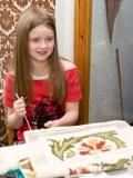 A young embroiderer demonstrates Canvas Work,